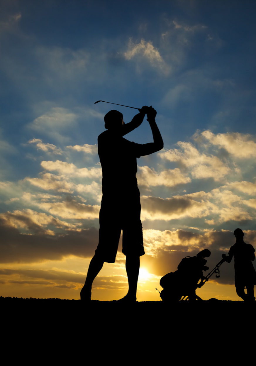 male golfer playing golf at sunset